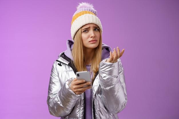 質問された複雑なかわいいブロンドのガールフレンドは奇妙なメッセージを受け取ります困惑した顔を上げて手を肩をすくめるリフト眉はスマートフォン、紫色の背景を保持する意味を理解できません。