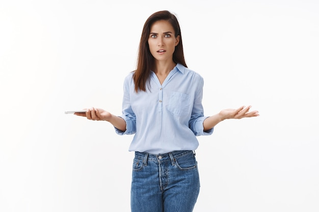 Опрошенная разочарованная взрослая бизнесвумен жалуется на сотрудников, получает плохие новости в текстовом сообщении, в тревоге держит смартфон, раскинув руки в стороны, смотрит вперед, сбитая с толку, озадаченная неприятная ситуация