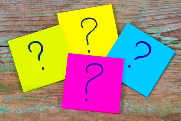Questions, decision making or uncertainty concept - a pile of colorful sticky notes with question marks on wooden background