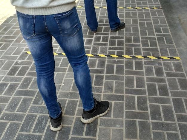 거리에 상점 큐. 사회적 거리. 음식을 위해 가게에 안전하게 들어가기를 기다리는 사람들의 발. 코로나 바이러스 전염병 동안 서로 거리를두고 바닥에 선을 안전하게 표시합니다.