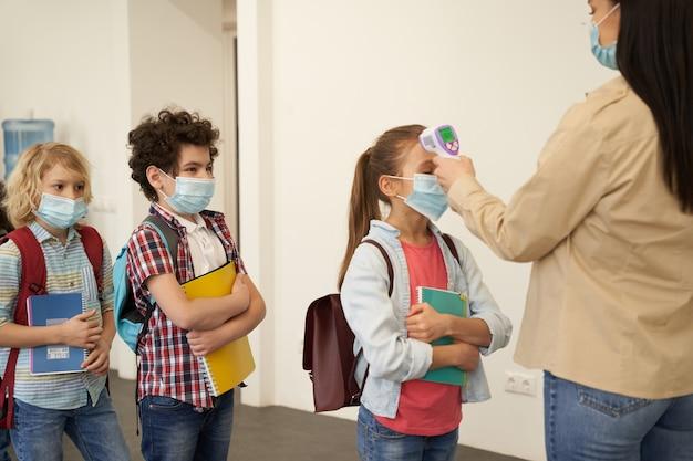 보호 마스크를 쓴 젊은 여교사가 체온을 측정하는 아이들과 함께 줄을 서다
