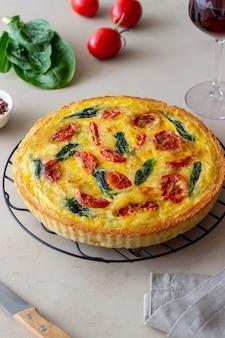 トマト、ほうれん草、チーズのキッシュまたはパイ。健康的な食事。ベジタリアンフード。フランス料理。