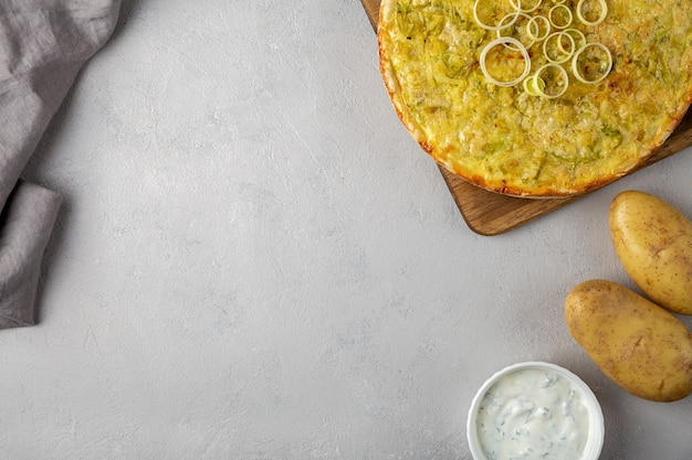 Quiche pie with leek, potatoes and cheese flat lay copy space on gray concrete background and ingredients cheese, sour cream, onion rings on round wooden cutting board.