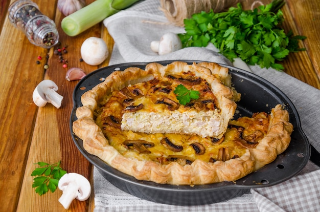Quiche on puff pastry with leek, meat and mushrooms