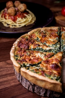 Quiche a savoury open tart  with spinach mushrooms cheese.