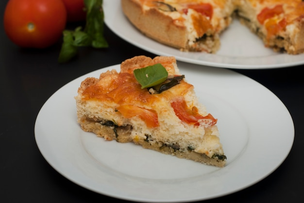 Quiche tart, pie with tomato, spinach, cheese.