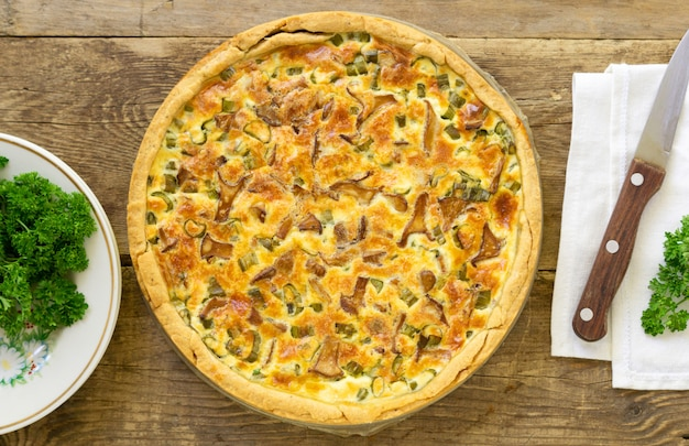 Quiche with chanterelles, herbs, and cheese on a wooden background