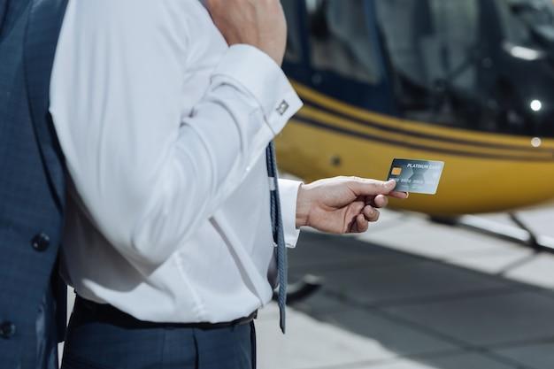 빠르고 편리합니다. 헬리콥터를 빌리는 데 사용했던 젊은 사업가의 손에있는 플래티넘 신용 카드에 초점