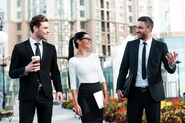 会議前の簡単な説明。お互いに話している3人の陽気な若いビジネスマン