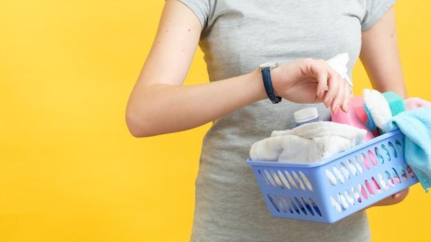 빠른 청소. 조직 된 아내 시간 관리. 시계를보고 공급의 바구니와 여자 몸통
