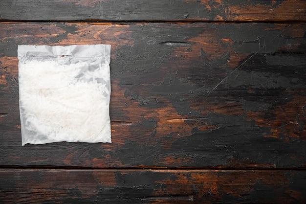 Набор мешков для быстрого приготовления риса на старом фоне темного деревянного стола, плоская планировка, вид сверху, с местом для текста