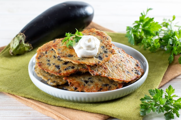 Quick and easy eggplant cutlets. fried eggplant cutlets with garlic on a wooden board. healthy veggie recipe. closeup