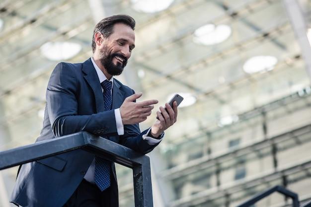 クイックメッセージ。手すりに寄りかかってメッセージを読んで笑顔のひげを生やしたビジネスマンのローアングル
