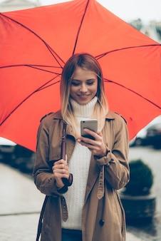 이동 중에도 빠른 메시지. 우산을 들고 거리를 걷는 동안 휴대 전화를보고 매력적인 젊은 웃는 여자
