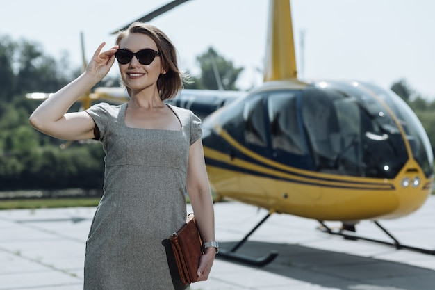 Quick travelling. beautiful female ceo standing at a helipad and being ready for flying to her business meeting on a helicopter