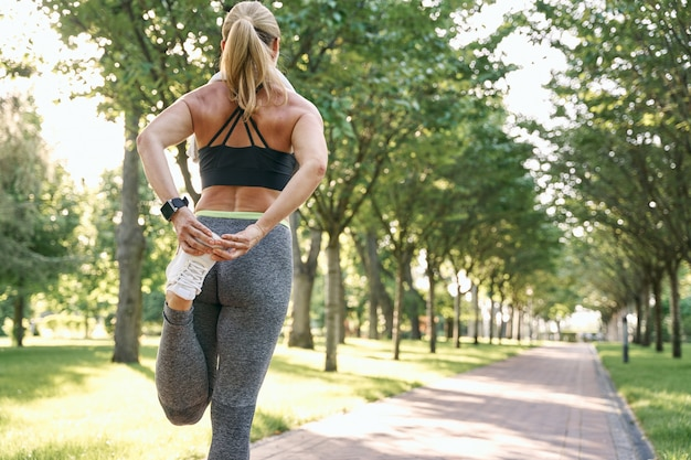 Quick warm up rear view of sporty woman stretching leg muscles during outdoor running workout in a