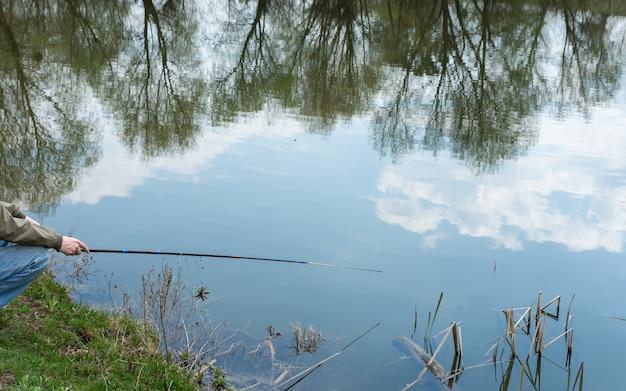 호수에서 조용하고 조용한 날, 어부가 물고기를 잡습니다.