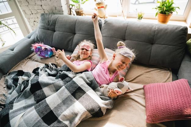 Tranquille bambine che si svegliano in una camera da letto in pigiama carino, stile casalingo e comfort