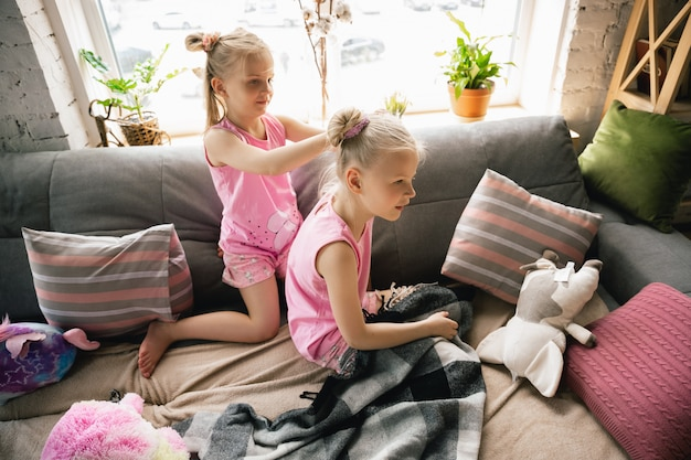 Quiet little girls waking up in a bedroom in cute pajamas, home style and comfort