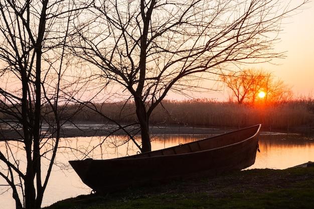 Тихий весенний закат на озере с лодкой, деревьями и снегом