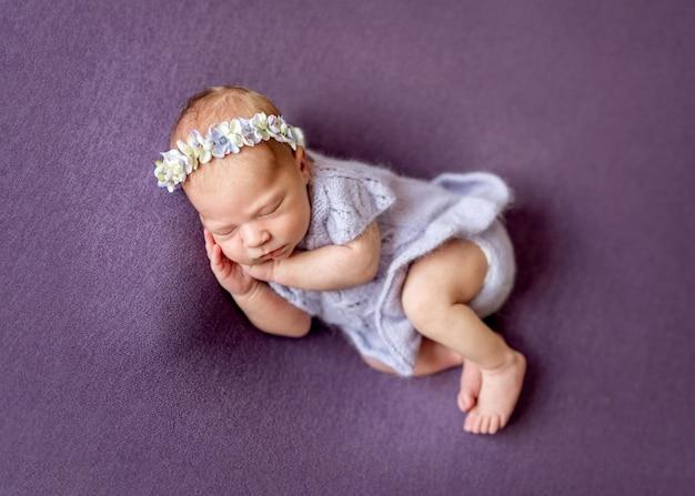Тихий усталый новорожденный ребенок на кровати