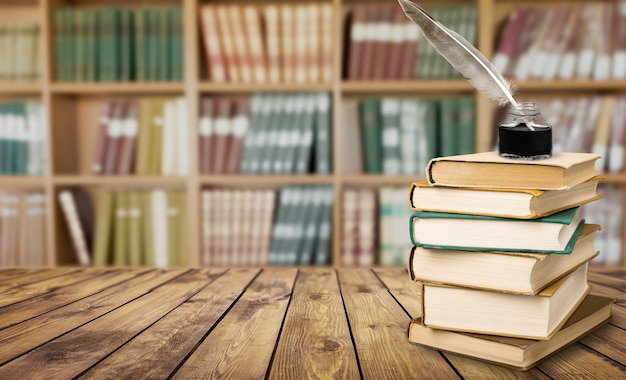 Гусиное перо и чернильница и старая книга