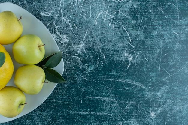 대리석 테이블에 접시에 마르멜로와 사과.