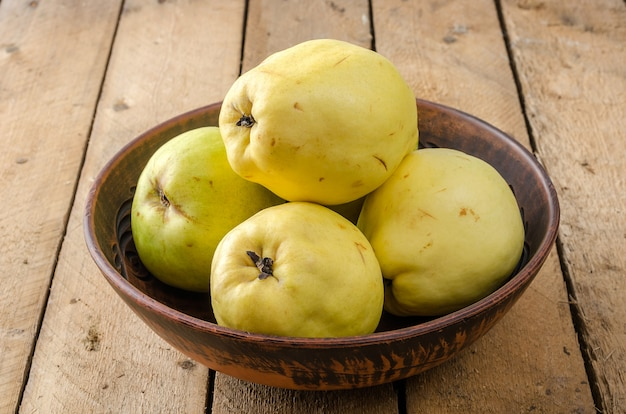 Quince in a large clay dish on a dark wooden background.