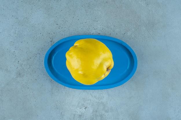 Айва на деревянной тарелке, на мраморном фоне. фото высокого качества