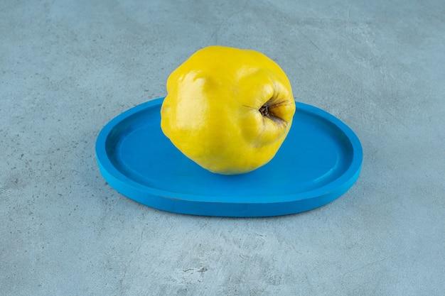 Айва на деревянной тарелке на мраморном столе.