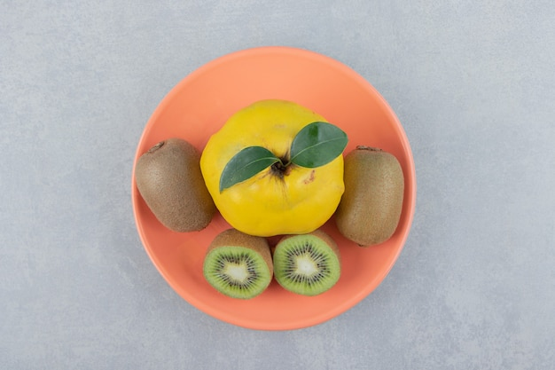 Quince and sliced kiwis on orange plate