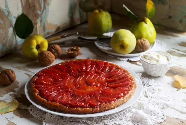 Quince tarte tatin served with whipped cream, quince fruits and walnuts on a wooden surface. rustic style.