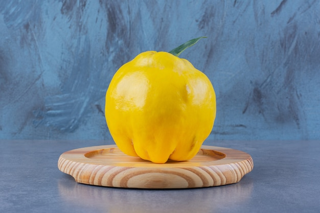 Quince on a wooden plate on the dark surface