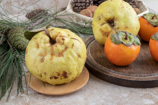 Quinces and oriental persimmons in a decorative arrangement on marble surface.