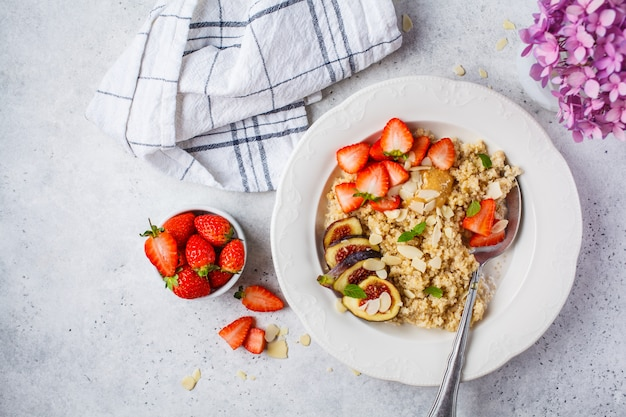 Quinoa breakfast porridge with strawberries and figs in white plate. healthy breakfast.