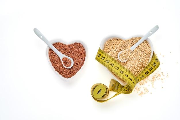 白いテーブル、上面図に分離されたハートの形のボウルに巻尺と亜麻仁のキノア穀物。ケトダイエットと適切な栄養の概念。