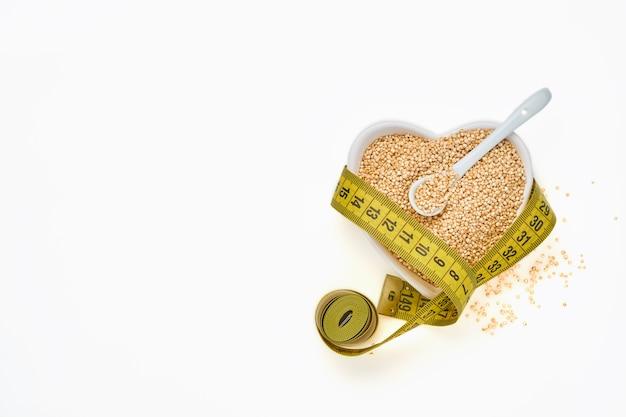 白いテーブル、上面図に分離されたハートの形のボウルに巻尺とキノアの穀物。ケトダイエットと適切な栄養の概念。