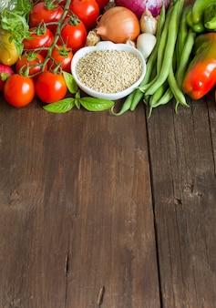 ボウルにキノアと木製のテーブルでの新鮮野菜をクローズアップ