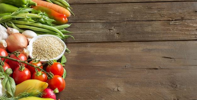 Киноа в миске и свежие овощи на деревянном столе