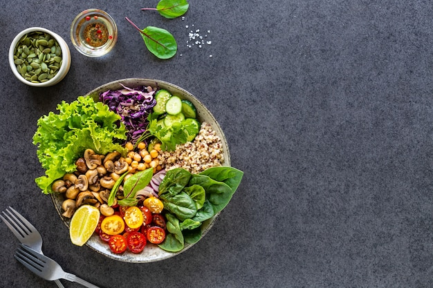 Quinoa, mushrooms, lettuce, red cabbage, spinach, cucumbers, tomatoes, a bowl of buddha on a dark surface, top view. delicious balanced nutrition concept