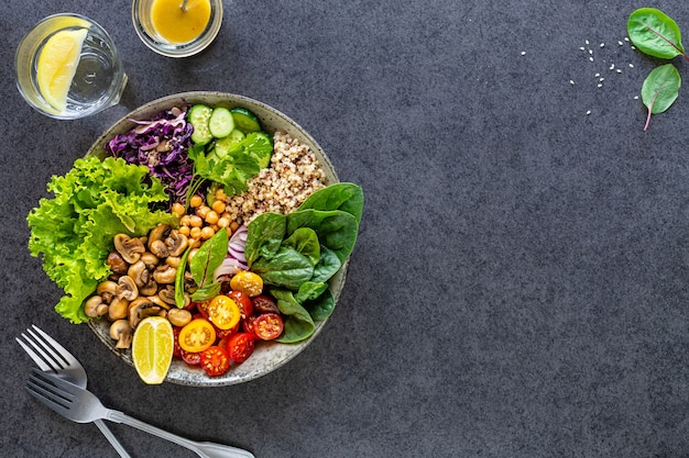 Quinoa, mushrooms, lettuce, red cabbage, spinach, cucumbers, tomatoes in a buddha bowl