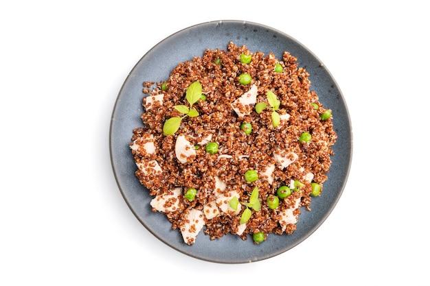 白い表面に分離されたセラミックプレート上のグリーンピースとチキンとキノアのお粥