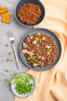 灰色のコンクリート表面とオレンジ色のテキスタイルのセラミックプレートにグリーンピースとチキンのキノアのお粥
