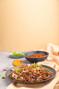 Quinoa porridge with green pea and chicken on ceramic plate on a gray concrete background.
