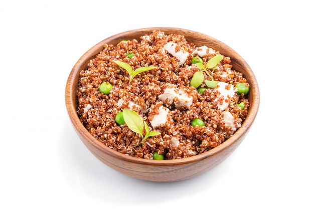 Quinoa porridge with green pea and chicken in wooden bowl isolated on a white background.