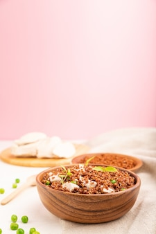 Quinoa porridge with green pea and chicken in wooden bowl on a white and pink background.