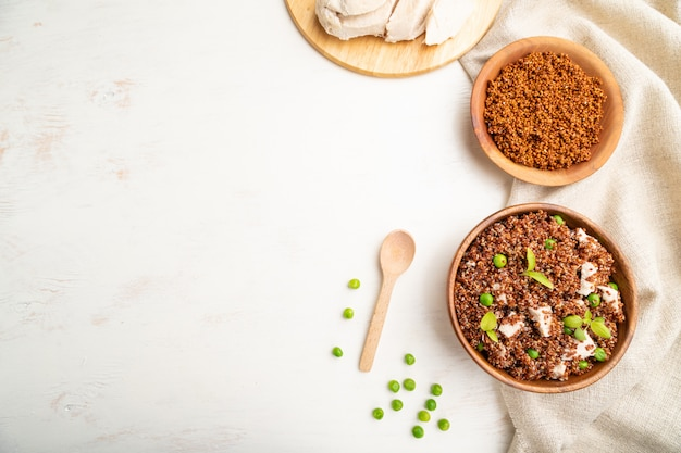 Quinoa porridge with green pea and chicken in wooden bowl on a white wooden background.