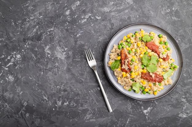 Каша из киноа с зеленым горошком, кукурузой и сушеными помидорами на керамической тарелке на сером бетонном столе. вид сверху, плоская планировка, копия пространства.
