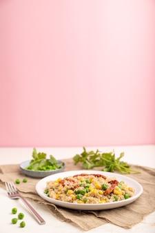 Каша из киноа с зеленым горошком, кукурузой и сушеными помидорами на керамической тарелке на бело-пастельно-розовой поверхности и льняной ткани
