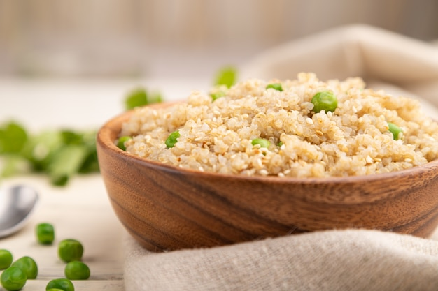 Quinoa porridge with green pea in wooden bowl on a white wooden background. side view, selective focus.
